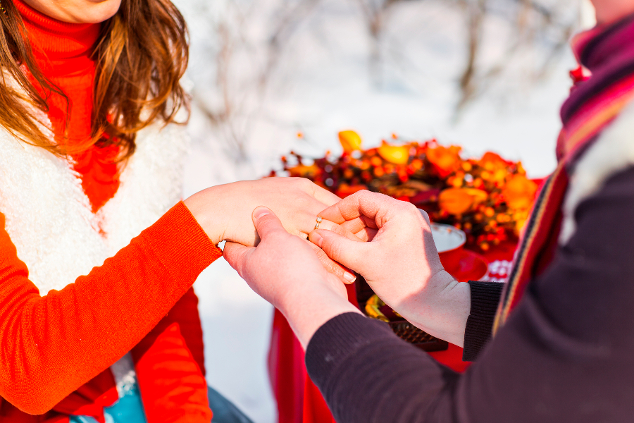 man putting wedding ring on woman hand. Christmas and New Year decoration - tree, gifts and wedding bouquet